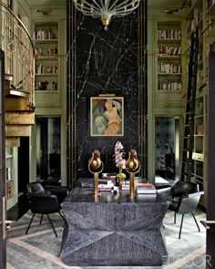 In the library of a Mercer Island, Washington home, olive green shelving and rug details contrast with negro marquina marble and brass.