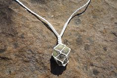White waxed cord macrame necklace with a soft green tumble stone caged pendant. This necklace can be tied around the back and slightly adjustable but the necklace length is fairly short and has been made for best fit to sit close between the collar bones.  Suitable for everyday wear it