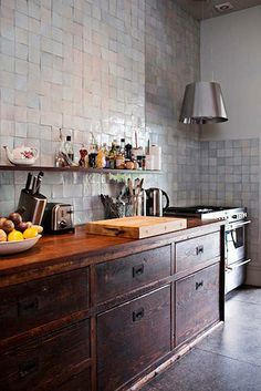 small tiles on the wall, wood cabinets, open shelving, butcher block counter