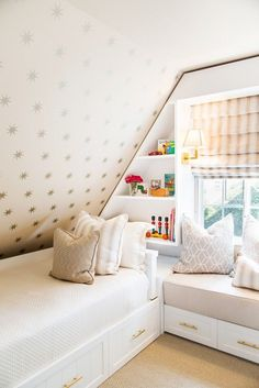 Kid's room with sloped ceiling, gold star wallpaper, and built-in bookshelves.