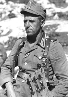 German mountain trooper in France. Note the edelweiss pin on his cap and the bandolier for MP-40 sub machine gun magazines.