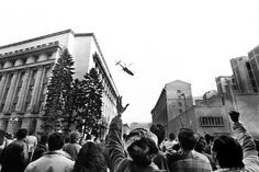 People gesturing towards a helicopter in which the country's communist dictator Nicolae Ceausescu fled the Romanian Communist Party Central Committee headquarters.