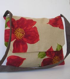 This rustic messenger is in a red poppy fabric and is accented with a dark brown strap.