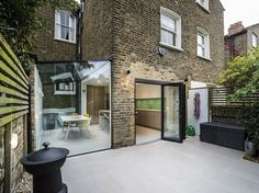 A side return extension in a conservation area in Hackney, designed by P.LANSTUDIO. The beautifully executed frameless glass structure sensitively complements the original brick house. The floor tiles seamlessly continue from the inside onto the patio even more connecting the internal space with the garden.
