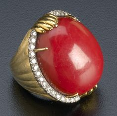Oxblood coral and diamond ring in 18k yg and wg, ca. 1970. Large oval coral cabochon within a row of diamonds, tapered band in a brushed ribbon design. Coral: 35 cts. (by formula), 27.5mm x 22.8mm x 12mm, diamonds: approx. .66 ct., 30.3 gs. GW,