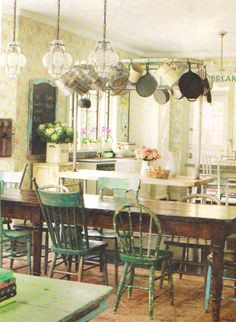 *green chairs. table. pot rack elevated with piping over work table made from same pipes.