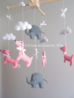 This nursery mobile is perfect to decorate your babys room, above a bed, or as a baby shower gift. Hangs 4 handmade Dachshunds and 2 Elephants from thick white cotton thread. They are suspended from a wooden hanger.  This mobile is not a toy and is intended for decorative purposes only.  If you want different colors, just convo me.    Mobile Size:  Height (from wood dowel to the lowest plush ): 50cm  Width: 35cm    Dachshunds measurements (cm): 14x10x1,5  Elephants measurements (cm)…