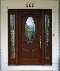small oval stained fiberglass door with sidelights.