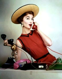 Evelyn Tripp wearing a sleeveless, red linen dress by Larry Aldrich with a hat from Lilly Dache. Photo by Erwin Blumenfeld, April 1953.