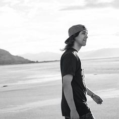 Vic Fuentes majestically walking across a beach with his luscious locks (hair) flowing freely in the beach breeze