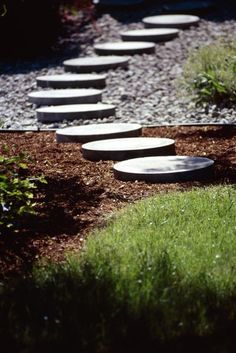 Round paver stones used for a garden walkway create a visually interesting juxtaposition with the straight, square sides of the walkway outline. Many companies that sell concrete mix also sell molds f Homemade Stepping Stones, Round Stepping Stones, Garden Stepping Stones, Paver Stones, River Rock Landscaping, Landscaping With Rocks, Backyard Landscaping, Landscaping Ideas, Walkway Ideas