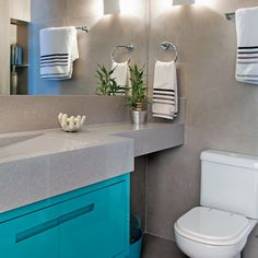 """Padronização organiza o olhar. Parede e piso do banheiro exibem o mesmo acabamento da casa toda: porcelanato acetinado Urban Concreto (90 x 90 cm, da Portinari). A bancada (1,75 mde comprimento, com larguras de 45 e 20 cm) é de Silestone alumínio, igual ao da cozinha. """"Os materiais, neutros, se repetem pelos ambientes, reforçando a unidade estética"""", aponta Rodrigo. O armário (90 x 40 x 45 cm) quebra a monotonia por meio do turquesa, cor forte e luminosa, vinda do acabamento de laca…"""