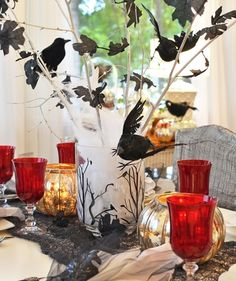 If you want to go all out for your Halloween party, this is the way to do it. Decorate branches with fake crows and black leaves and then place them in a mason jar filled with sand or pebbles. Place the mason jar inside a large hurricane or vase and fill the inside with cotton batting. Add a lace black table runner and vintage dishes and candleholders to finish the spooky look.