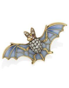 An Art Nouveau enamel, diamond and ruby bat brooch, circa 1900.