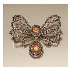 TOPAZ AND DIAMOND DEVANT DE CORSAGE, PORTUGUESE, SECOND HALF OF THE 18TH CENTURY. Designed as a stylized open work tied ribbon bow, centering on a circular cluster, suspending a pear-shaped drop, set with foil backed mixed-cut topaz, table- and rose-cut diamonds, detachable drop.