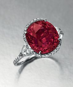 Set with a cushion-cut ruby, weighing approximately 6.25 carats, flanked on either side by a shield-shaped diamond, within a circular-cut di...