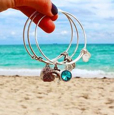 ALEX AND ANI Sand Dollar Charm Bangle | Dolphin Charm bangle | Birthstone Charm Bangle | Sand dollars move with the sea. They embody energies of transformation, freedom, and the strength to change with grace. Legend has it that five doves of peace can be found within a sand dollar's shell. Some say these are the five angels that sang to the wise men. Trust the process and receive the blessings that flow toward you.