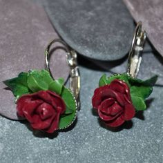 Welcome to Musa Natura, a place where you will find lots of handmade pieces inspired by Nature. Each one lovingly crafted by hand and made to order.  This listing is for a beautiful pair of lever back pair of Dark Red Rose Earrings.  The Roses and Leaves have been hand sculpted from Polymer Clay, the leaves individually painted by hand and set on to the Silver tone earrings.  Each earring measures approximately 1 1/4 inch (approximately 3 cm) in length, from the hoop at the top of the ea...