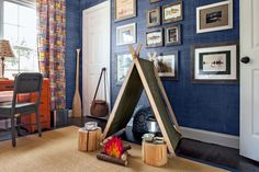 We love this fun bedroom for an outdoor-loving kid. Mom and dad fashioned the tent from an army blanket, and saved money by scouring resale shops, Etsy, and eBay for woodsy elements, such as tree-stump seats.   Photo: Helen Norman