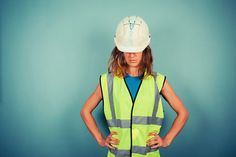 A young female engineer is wearing a high vis vest and a hardhat Construction Birthday Parties, Young Female, Hard Hats, Engineering, Vest, How To Wear, Characters, Goals, Architecture