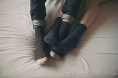 Intertwined feet cute couples bed feet snuggle cozy socks