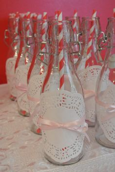 Simple idea -- glass bottle with a doily and a ribbon - cute for baby shower - add a flower in each one!