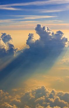 High in the sky, floating amongst the clouds with rays of sun beaming through the white tufts.