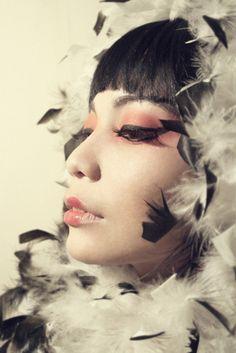 Old Hollywood glamour fashion photo.  Asian model.  Eyeliner and boa.