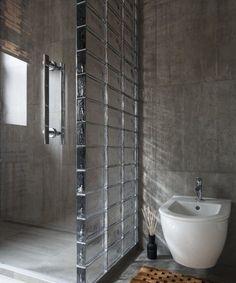 Płytki ścienne o surowym wyglądzie i luksfery tworzą tu industrialny klimat łazienki.