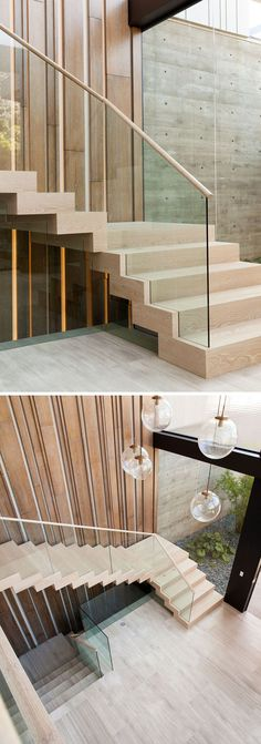 In this modern house, light wood stairs lead up to the second floor of the home., and a vertical wood accent wall with hidden lighting helps to emphasize the height of the foyer.: