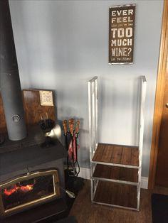 Brushed aluminum frame indoor firewood rack with walnut finish shelves for paper, kindling, and firewood.