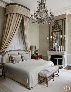 A luxe master bathroom featuring a canopy bed and an Italian chandelier from the 1880s | archdigest.com