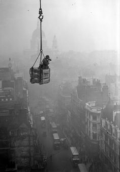 """A photographer dangles over Fleet Street, with St Paul's in the background.    From the photo book """"London: Portrait of a City""""    #photobook #london #blackandwhite #aerial"""