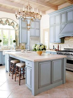 Perfectly French Kitchen // Earthy elements such as limestone, marble, and pickled poplar on the ceiling balance elegant appointments like the hand-forged iron chandelier and custom window treatment. Blue cabinets with a gray undertone create a peaceful, and perfectly French, look.