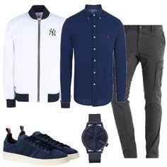 La camicia a maniche lunghe blu è abbinata al bomber bianco in tessuto tecnico, con profili di maglia blu. I pantaloni cargo sono grigio scuro e le sneakers di camoscio sono blu. Per ultimo un orologio in acciaio e cinturino di pelle, blu.