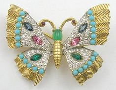 Pretty Jomaz vintage butterfly brooch with textured gold tone wings pave set with clear rhinestones, and decorated with rows of turquoise glass cabochons and sapphire, pink and green marquis rhinestones. Jade green oval cabochon head with red rhinestone in the antennae. Attributed Jomaz.