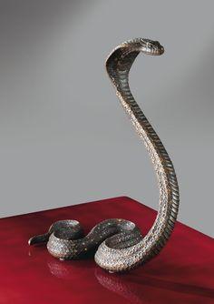 JEAN DUNAND (1877 - 1942). 'NAJA AVANÇANT', A PATINATED BRONZE SCULPTURE BY JEAN DUNAND, CIRCA 1914. SIGNED. sculpture en bronze à patine brun, rouge et or. Signée Jean Dunand  au revers. Hauteur : 30,7 cm (12 in.) Largeur : 14,3 cm (5 5/8 in.) Profondeur : 23,5 cm (9 1/4 in.). -Sotheby's-