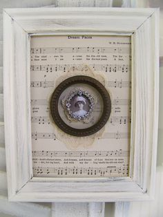 Lovely white collage or grouping of everything vintage and shabby. A background of sentimental sheet music, topped with antique lace, an old round frame
