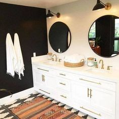 black accent walls bathroom with round mirrors