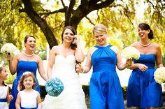 Bridesmaids : bright blue dresses with white hydrangea bouquets