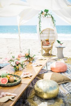 Tulum inspired boho beach birthday party featuring tropical flowers, patterned floor pillows, and fresh fruit centerpieces.