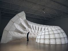 Capacitor by John Grade  Set within Capacitor's lightweight skeleton – perforated fabric skins stretch over wooden frames – embedded lights intensify based on outside air temperature. Responding to wind speed, the entire structure grows or recedes.
