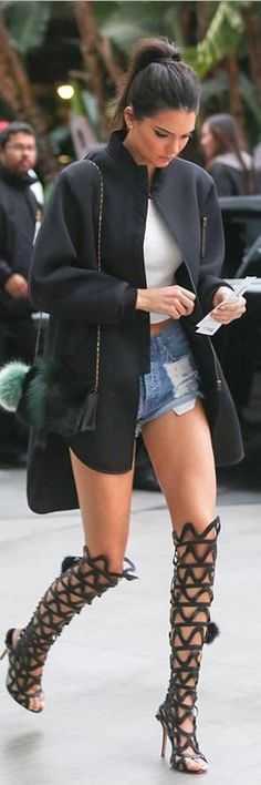 Model street style | Short denim shorts with roman sandals and straight black coat