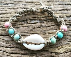 Hemp Macrame Bracelet with Cowrie Shell & Timber Beads  This is a hemp twine bracelet with beautiful Mermaid Cowrie shells and antiqued glass beads, woven using the square knot macrame stitch. This necklace clasps easily around the neck using a strong wooden bead through the knot technique. It reacts well to water, and can be worn on the beach and in the ocean, however we do recommend removing any jewellery before swimming in the surf. Specs: •Cowrie Shells •Timber Beads •Polished Hungarian…