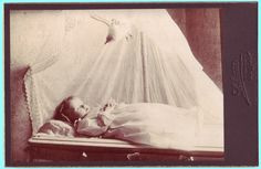 A cabinet card showing a young girl laid out with a stuffed bird suspended above her. The bird presumably is meant to represent either her departing soul ascending, in which case one might expect it to be facing the other direction, or the Holy Spirit descending.    Photographed by Schmidt of 7116, Broadway, Buffalo [New York].