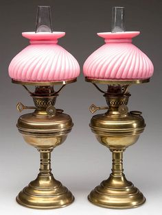 "PAIR OF BRASS MINIATURE LAMPS, pedestal, weighted bases, matching pair of pink cased-glass swirl umbrella shades. Period burners marked ""Cintra"", shade rings and colorless chimneys. Burner has a key handle to lift shade to light burner."