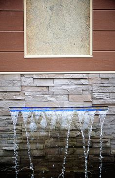 LED-lit waterfalls trickle soothingly into a moat around the lounge area.  Deck Design by Paul Lafrance Design.