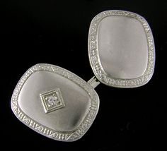 These white gold cufflinks shimmer with a rich, frosty patina that contrasts beautifully with the brightly engraved Art Deco borders and sparkling diamonds.  A nice example of the striking white-on-white designs of the 1930s.  Created by Kohn & Company in 14kt gold, circa 1930.