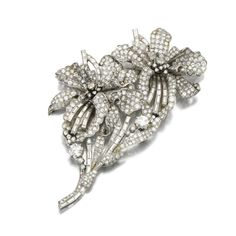 DIAMOND BROOCH, 1950S Of floral design, set with circular-, single-cut and baguette diamonds.