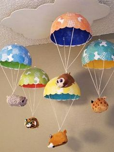 """Made this cute mobile with animals floating down in parachutes from the cloud for our grand baby. Used paper mache on balloon forms with tissue paper on first four layers and finished with scrapbook paper cut into 1.5"""" circles for top layer."""